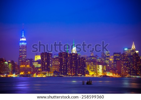 New York City skyline under dark blue night sky - stock photo