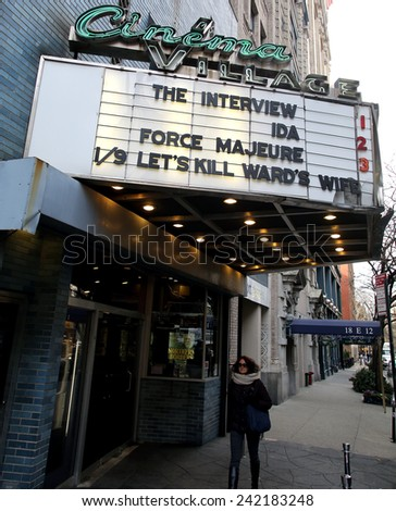 NEW YORK CITY - TUESDAY, DEC. 30, 2014: A woman walks under a movie theater marquee showing Sony Pictures film The Interview. The film prompted a North Korean government  computer hack of Sony - stock photo