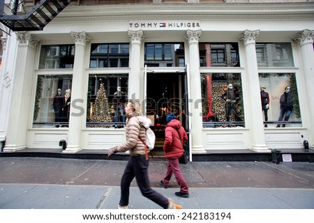 NEW YORK CITY - TUESDAY, DEC. 30, 2014: Pedestrians walk past a Tommy Hilfiger store. Tommy Hilfiger is an American fashion, apparel, design, fragrance retail company - stock photo