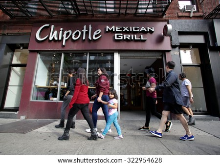 NEW YORK CITY - TUESDAY, SEPTEMBER 22, 2015: Pedestrians walk past a Chipotle Mexican fast food restaurant.  Chipotle Mexican Grill, Inc. is a chain of restaurants. - stock photo