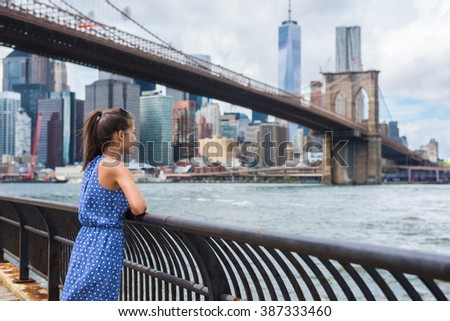 New York city urban woman enjoying view of Brooklyn bridge and NYC skyline living a happy lifestyle walking during summer travel in USA. Female Asian tourist in her 20s. - stock photo