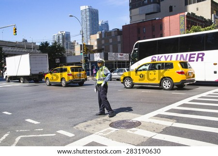 NEW YORK CITY,USA-AUGUST 5,2013:city life in a metropoli.A  policeman directs traffic in midtown Manhattan during a sunny day - stock photo