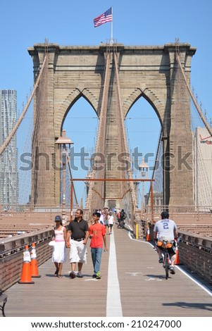 New York City, USA - August 10, 2014: Pedestrians and bicyclists going back and forth across the Brooklyn Bridge in New York City.  - stock photo