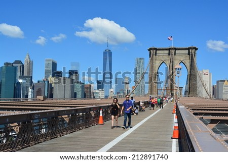 New York City, USA - August 24, 2014: People walking across the Brooklyn Bridge with the Lower Manhattan skyline in the background in New York City.  - stock photo