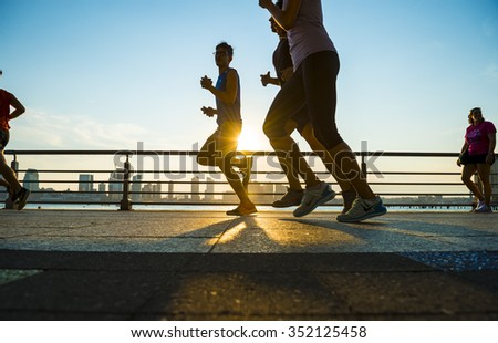 NEW YORK CITY, USA - AUGUST 15, 2015: Silhouettes of men run at sunset on the Hudson River boardwalk. - stock photo
