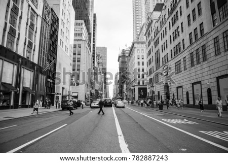 NEW YORK CITY, USA - CIRCA JUNE, 2016: A view down a New York City Street of people crossing the road. Manhattan, USA.