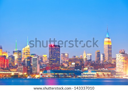 New York City, USA colorful night skyline panorama with   reflected illuminated landmark buildings in downtown business and residential districts
