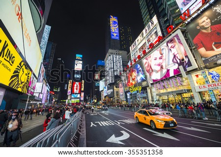 NEW YORK CITY, USA - DECEMBER 22, 2015: Yellow New York taxi passes crowds gathering under the bright lights of Times Square in the build-up to New Year's Eve. - stock photo