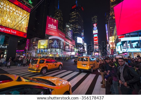 NEW YORK CITY, USA - DECEMBER 22, 2015: Yellow New York taxis pass crowds gathering under the bright lights of Times Square in the build-up to New Year's Eve.