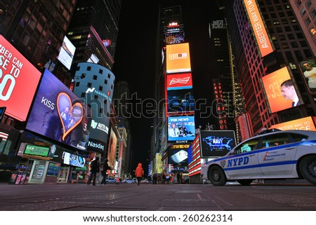 NEW YORK CITY, USA - FEBRUARY 25, 2015: Cityscape of Times Square late at night with a few pedestrians watching the giant billboards, neon lights and an NYPD car on February 25, 2015 in New York City.