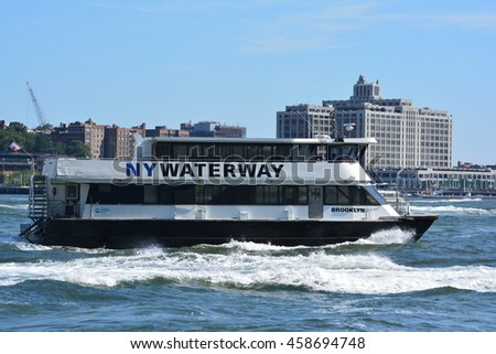 New York City, USA - July 24, 2016: New York Waterway ferry cruising along the East River with Brooklyn in the background in Lower Manhattan in 2016 in New York City.