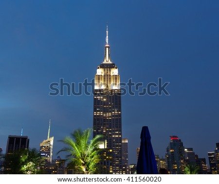 New York City, USA - July 13, 2015: View of the famous Empire State Building at sunset. This view is from the rooftop of the 230-fifth Bar. - stock photo