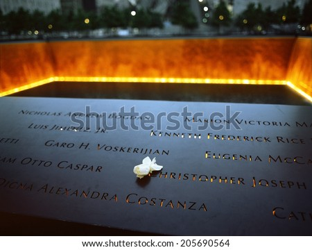 New York City, USA - June 24, 2014: 9/11 Memorial at Ground Zero, Manhattan, commemorating the terrorist attack of September 11, 2001. Flowers near the names of victims engraved in the bronze parapet. - stock photo
