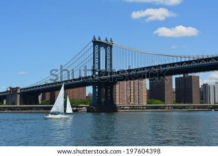 NEW YORK CITY, USA - June 6, 2014: Sailboat on the East River passing under the Manhattan Bridge.  - stock photo