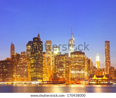 New York City  USA, lights on the buildings in lower Manhattan are reflected in the water during colorful sunset - stock photo