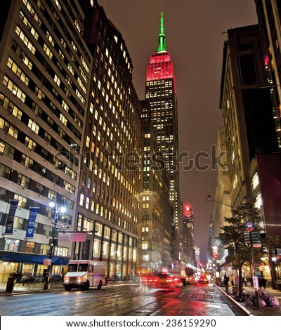 NEW YORK CITY, USA - NOV 13, 2014: Empire State Building, in red, white and green colors at night is a draw to New York tourism and is an iconic building of New York and America  - stock photo