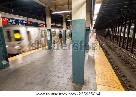 NEW YORK CITY, USA - NOVEMBER 17, 2014 : A bride model posing in New York City Subway when train leaving subway station and people pass by. - stock photo