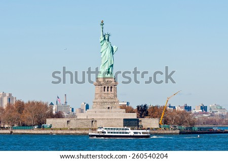 NEW YORK CITY, USA - NOVEMBER 18: The Statue Cruises boat with tourists passing the Statue of Liberty at November 18, 2011, NYC. - stock photo