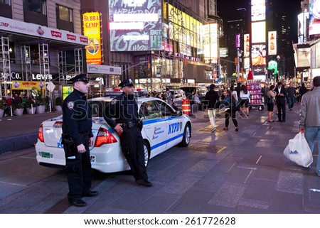 NEW YORK CITY, USA - OCT 9, 2014 : Police car and policemen in the Times Square. Times Square is major commercial intersection and one of most visited and protected tourist attractions in the world. - stock photo