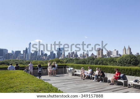 New York City, USA, 14 september 2015: visitors enjoy sunshine and view on manhattan skyline over central park on roof of metropolitan museum of art - stock photo