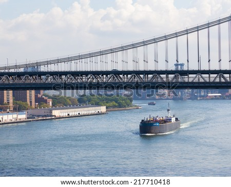 NEW YORK CITY, USA - 1ST SEPTEMBER 2014: A Large Cargo ship below Manhattan Bridge during the day down the East River