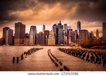 New York City view of lower Manhattan financial district under dramatic sky from across East River with wood pilings - stock photo