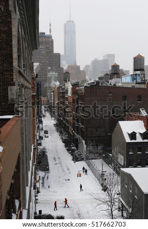 NEW YORK CITY - WINTER STORM 2014: People make their way across Spring street in the Soho section of Manhattan by foot and skis during a storm, with One World Trade Center looming in lower Manhattan.