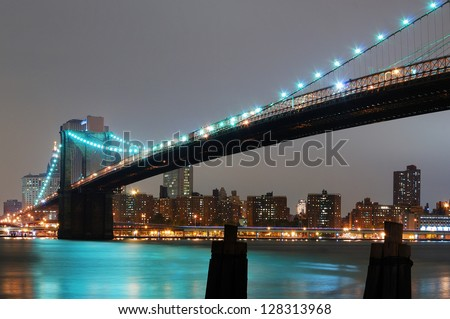 New York City with Brooklyn Bridge at night over Hudson River. - stock photo