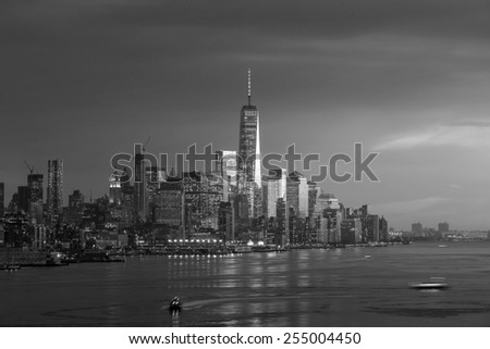 New York City with skyscrapers illuminated over Hudson River panorama, including the One World Trade Center in black and white