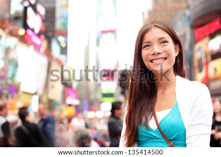 New York City woman as Times Square tourist or young casual woman visiting. Beautiful young happy smiling multicultural Caucasian Asian woman on Manhattan, New York City, New York, USA. - stock photo