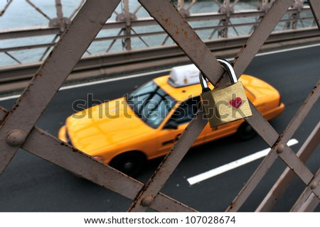 New York City yellow taxi cab drive pass by padlock with a heart symbol on Brooklyn Bridge in Manhattan New York, USA. - stock photo