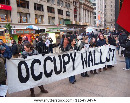 NEW YORK - DEC 12: Unidentified Occupy Wall Street protesters march to protest Goldman Sachs on December 12, 2011 in New York City, NY. Protests against the financial system took place nationwide. - stock photo