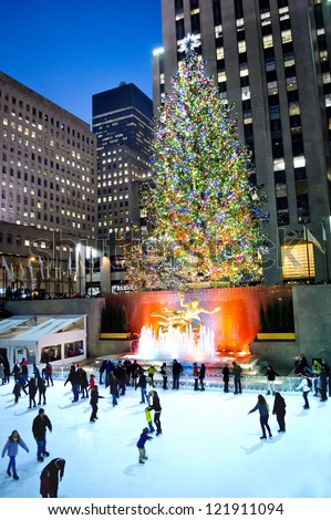 NEW YORK - DECEMBER 14: Ice skaters enjoy the rink around the famous Rockefeller Center Christmas tree at night on December 14, 2012 in New York City. - stock photo