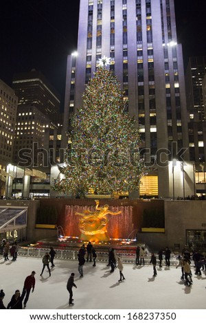 NEW YORK - DECEMBER 18: Tourists and ice skaters visit the famed Rockefeller Center Christmas tree on December 18, 2013 in New York City. - stock photo