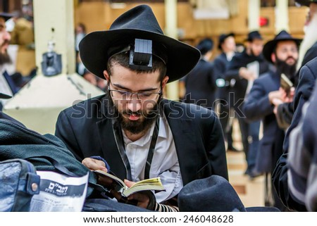 NEW YORK - DECEMBER 26: Ultra Orthodox Jewish man praying during service in the famous 770 Chabad Lubavitch headquarter and home to last Chabad leader Menachem Mendel Schneerson on December 26 2014 - stock photo