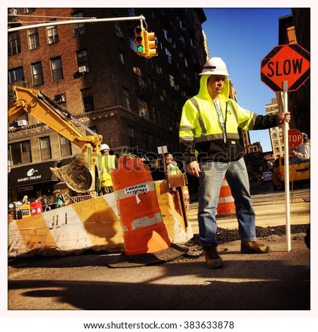 NEW YORK - 28FEB16: An unidentified construction worker holds a Slow sign to control traffic on corner of Waverly St and University Pl on February 28, 2016 in NYC. - stock photo