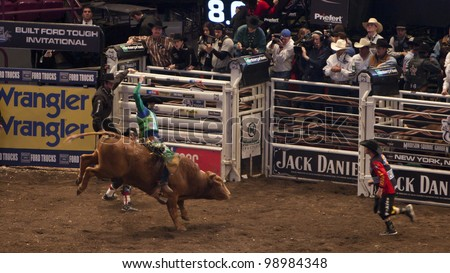 NEW YORK - JAN 10: An unidentified bull rider tries to stay on the bull for 8 seconds during the Professional Bull Rider tournament on January 10, 2009 in New York, NY. - stock photo