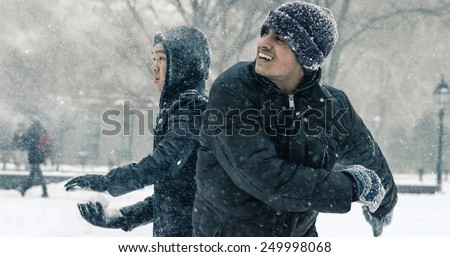 NEW YORK - JAN 26, 2015: Asian and Indian man throwing snow ball in snowball fight in blizzard in Washington Square Park in Manhattan New York. The nor'easter snowstorm of 2015 was named Juno. - stock photo