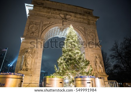 NEW YORK - JAN 3, 2017: recycling bins and trash cans in front of Washington Square Park North Christmas tree under arch at night in NYC. All public parks in the city provide garbage waste cans.
