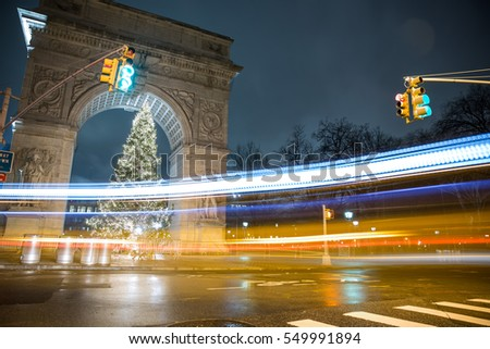 NEW YORK - JAN 3, 2017: streaks of light from car driving in long exposure crossing Washington Square Park arch and Christmas tree at night in NYC. WSP is a popular public space in Manhattan.