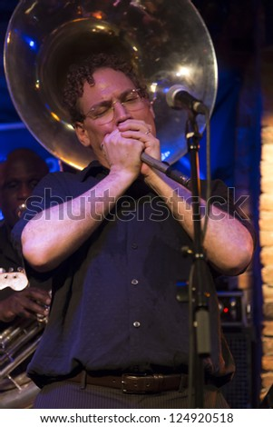 NEW YORK - JANUARY 12: Wade Schuman harmonica performs with Hazmat Modine band on stage as part of NYC Winter Jazz Festival at The Bitter End on January 12, 2013 in New York City - stock photo
