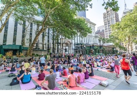 NEW YORK - JUL 22:  Group of people doing exercises in the Bryant Park on July 22, 2014 in New York. Bryant Park is a 9.603-acre public park located in the New York City borough of Manhattan - stock photo