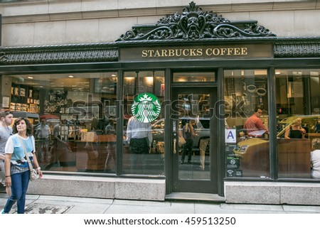 New York, July 26, 2016: A store front for a Starbucks Coffee shop location in Manhattan with people walking by and sitting inside.