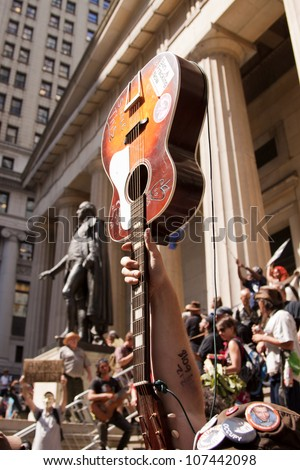 NEW YORK-JULY 11: An Occupy Guitarmy protester holds up his guitar in front of Federal Hall during the #99MileMarch from Philly to NYC on July 11, 2012 in New York, NY. - stock photo