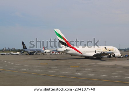 NEW YORK -JULY 10: Emirates Airline and Singapore Airlines Airbus A380 jets at JFK Airport  in NY on July 10, 2014. The Airbus A380 is a double-deck, wide-body, world's largest passenger airliner  - stock photo