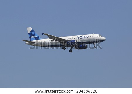 NEW YORK - JULY 8: JetBlue Airbus A320 in New York sky before landing at JFK Airport on July 8, 2014  JetBlue Airways is an American low-cost airline with main base at JFK International Airport - stock photo