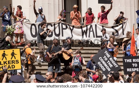 NEW YORK-JULY 11: Occupy Guitarmy protesters rally and play music in front of Federal Hall across from the NY Stock Exchange at the #99MileMarch from Philly to NYC on July 11, 2012 in New York, NY. - stock photo
