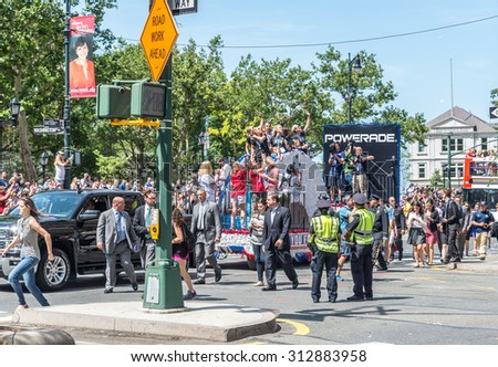 NEW YORK - JULY 10: Thousands of fans cheer as the World Cup-winning US women's soccer team make their way up the The Canyon of Heroes along Broadway during the parade on July 10, 2015 in NYC. - stock photo