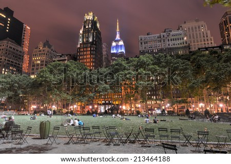 NEW YORK - JULY 9, 2014: View of Bryant Park and Manhattan Skyscrapers at Night. People relaxing on the grass. - stock photo