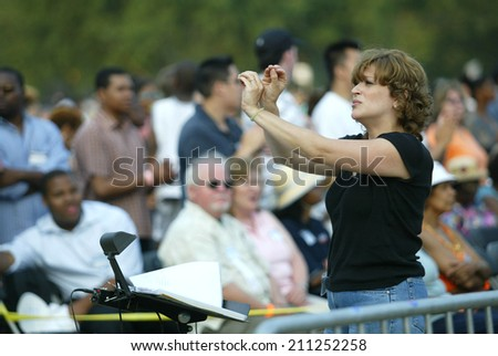 NEW YORK - JUNE 25:  A sign language interpreter gestures during the Greater New York Billy Graham Crusade in Flushing Meadow Corona Park June 25, 2005 in the Queens borough of New York City.  - stock photo
